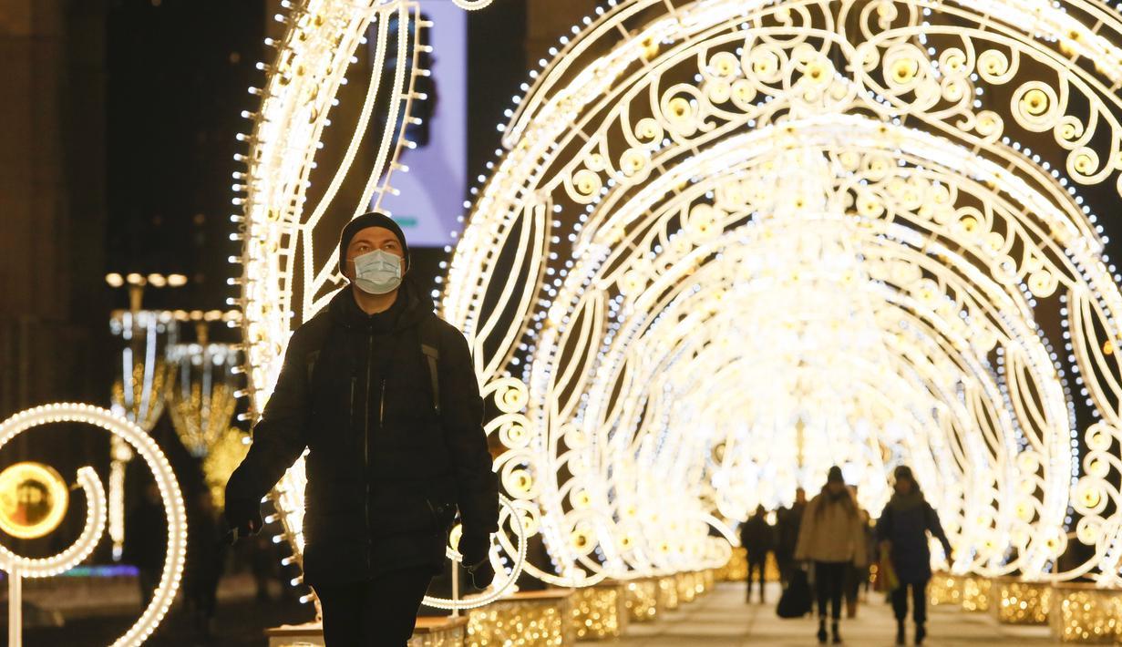 Seorang pria berjalan melewati lorong berhias lampu yang dipasang untuk menyambut libur Tahun Baru dan Natal Ortodoks di Moskow, Rusia, pada 29 Desember 2020. (Xinhua/Alexander Zemlianichenko Jr)