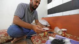 Warga Suriah, Hadheefa al-Shahadh membuat masker gas untuk menghadapi serangan pasukan pemerintah di Desa Maud Shurin, Provinsi Idlib, Selasa (11/). Masker dia buat dari gelas kertas, arang, kayu, kapas, plastik nilon, dan plester. (OMAR HAJ KADOUR/AFP)