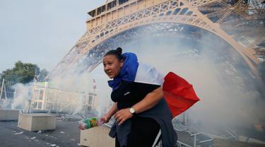 Seorang demonstran berlari menghindari gas air mata yang ditembakan polisi di bawah Menara Eiffel di dekat zona penggemar Paris sebelum laga Portugal vs Prancis di Final EURO 2016 di Prancis (10/6). (REUTERS/Stephane Mahe)