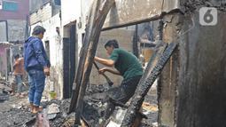 Warga melihat sisa permukiman yang terbakar di Jalan Keadilan Dalam, Taman Sari, Jakarta Barat, Senin (19/4/2021). Kebakaran permukiman padat tersebut mengakibatkan sebanyak 200 rumah hangus terbakar dan sekitar 1.000 warga terpaksa mengungsi. (Liputan6.com/Herman Zakharia)