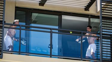 Petenis pria peringkat satu dunia, Novak Djokovic melakukan latihan di balkon hotel, Adelaide, Australia, Rabu (20/1/2021). (Foto: AFP/Morgan Sette)