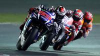 Pebalap Movistar Yamaha, Jorge Lorenzo, memimpin di depan Andrea Dovizioso dan Marc Marquez pada balapan MotoGP Qatar di Sirkuit Losail, Senin (21/3/2016) dini hari WIB. (AFP/Karim Jaafar)