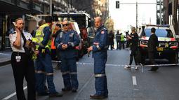 Polisi berjaga di tempat kejadian setelah seorang pria menikam wanita dan berusaha menikam orang lain di pusat kota Sydney (13/8/2019). Dilaporkan satu wanita tewas di salah satu blok lain tetapi tidak jelas kematian wanita tersebut terkait insiden penikaman atau bukan. (AFP Photo/Saeed Khan)
