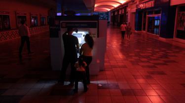 Warga menggunakan mesin ATM di pusat perbelanjaan ketika pemadaman listrik di San Juan, Puerto Rico, Rabu (21/9). Kebakaran yang terjadi di pembangkit listrik Puerto Rico menyebabkan 1,5 juta penduduk pulau itu hidup tanpa listrik. (REUTERS/Alvin Baez)