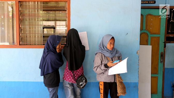 Sejumlah siswi melakukan pendataan pada hari pertama sekolah di SMP Negeri 6 Palu, Sulawesi Tengah, Senin (8/10). Pascagempa dan tsunami Palu, pihak sekolah melakukan pendataan untuk mengetahui jumlah siswa sekolah. (Liputan6.com/Fery Pradolo)