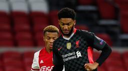 Bek Liverpool, Joe Gomez mengontrol bola di depan pemain Ajax Amsterdam, David Neres pada pertandingan pertama Grup D Liga Champions 2020 di Johan Cruijff Arena, Kamis (22/10/2020) dini hari WIB. Liverpool susah payah menang tipis 1-0 di kandang Ajax. (AP Photo/Peter Dejong)