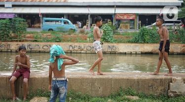 Anak-anak berenang di aliran Sungai Kalimalang, Jakarta, Selasa (18/8/2020). Keterbatasan ekonomi menyebabkan anak-anak tersebut memanfaatkan Sungai Kalimalang sebagai tempat berenang, meskipun berbahaya bagi keselamatan dan kesehatan mereka. (Liputan6.com/Immanuel Antonius)