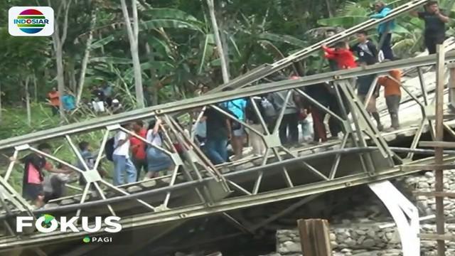 Truk sarat muatan material bangunan ini pun terguling setelah tiang penyanggah jembatan roboh akibat tidak kuat menahan beban di atasnya.