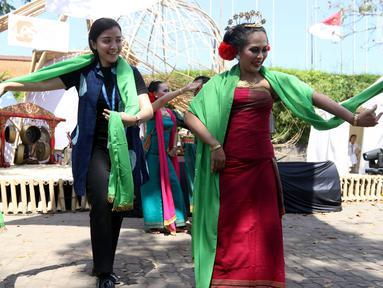 Seorang delegasi ikut menari pada pertunjukkan budaya nusantara di arena Pertemuan Tahunan IMF - World Bank 2018 di Nusa Dua Bali, Jumat (12/10). BeKraf dan LPS menyajikan beragam seni dan budaya Nusantara. (Liputan6.com/Angga Yuniar)