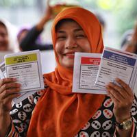 Warga menunjukkan contoh surat suara saat simulasi pemungutan dan pencoblosan surat suara Pemilu 2019 di Taman Suropati, Jakarta, Rabu (10/4). Simulasi pemungutan surat suara dilakukan untuk meminimalisir kesalahan dan kekurangan saat pencoblosan pemilu pada 17 April nanti (Liputan6.com/Johan Tallo)