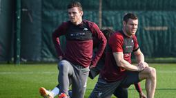 Pemain Liverpool, James Milner dan Andrew Robertson, saat sesi latihan jelang laga Liga Champions di Melwood, Liverpool, Senin (8/4). Liverpool akan berhadapna dengan Porto. (AFP/Paul Ellis)