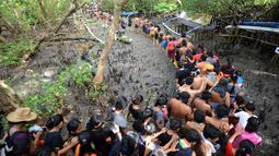 Warga berjalan menyusuri hutan mangrove saat mengikuti tradisi mandi lumpur atau mebuug-buugan di Desa Kedonganan, Denpasar, Bali, Jumat (8/3). Mebuug-buugan diikuti ratusan warga ini digelar di hutan mangrove. (Sonny Tumbelaka/AFP)