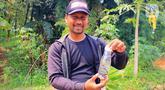 Petugas keamanan Perumahan Citayam Village, Anwar Irawan memperlihatkan anak ular kobra yang  ditangkap warga saat kerja bakti di Kab. Bogor, Sabtu (14/12/2019). Kerja bakti untuk membersihkan lingkungan sekaligus melakukan penyisiran pencarian induk ular kobra. (merdeka.com/Magang/Muhammad Fayyadh)