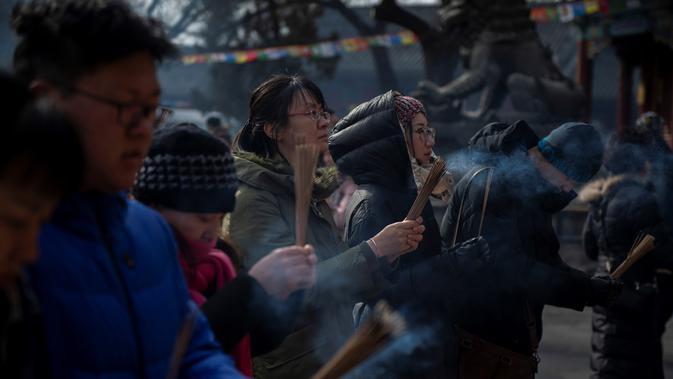 Sejumlah warga berdoa untuk keberuntungan pada hari kelima Tahun Baru Imlek di Yonghegong, atau Kuil Lama di Beijing (9/2). Warga China di seluruh dunia menyambut Tahun Babi pada 5 Februari.  (AFP Photo/Nicolas Asfouri)#source%3Dgooglier%2Ecom#https%3A%2F%2Fgooglier%2Ecom%2Fpage%2F%2F10000