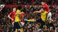 Bek Manchester United, Harry Maguire, berebut bola dengan bek Arsenal, Sokratis Papastathopoulos, pada laga Premier League di Stadion Old Trafford, Manchester, Senin (30/9). Kedua klub bermain imbang 1-1. (AFP/Paul Ellis)