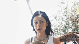 Berlibur di Ambon, Clara tidak melewatkan kesempata untuk mencoba kelapa muda segar di pantai. Menggunakan tank top putih, dengan celana hitam, penampilannya semakin lengkap dengan tas sandang bermotif khas nusantara. (Liputan6.com/IG/clarabernadeth)