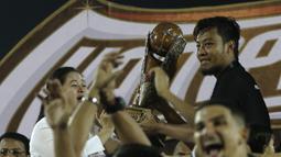 Kapten Arema FC, Hamkah Hamzah, merayakan gelar juara Piala Presiden 2019 usai menaklukkan Persebaya Surabaya di Stadion Kanjuruhan, Jumat (13/4). Arema FC menang 2-0 atas Persebaya. (Bola.com/Yoppy Renato)