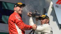 Pembalap Mercedes, Lewis Hamilton, menyemprotkan sampanye kearah pembalap Ferrari, Sebastian Vettel saat berselebrasi mejuarai GP Hungaria di Sirkuit Hungaroring, Mogyorod, (29/7). (Zoltan Balogh/MTI via AP)