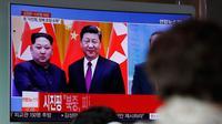 Warga menonton berita yang menyiarkan kunjungan kejutan Pemimpin Korea Utara Kim Jong-un ke China di Seoul Railway Station, Korea Selatan, Rabu (28/3). Ini merupakan lawatan pertama Kim Jong-un sejak menjabat pada 2011. (AP Photo/Lee Jin-man)