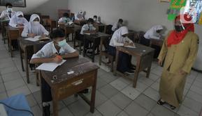 Guru mengajar para murid saat pelaksanaan uji coba pendidikan tatap muka (PTM) di SMPN 15, Kota Bogor, Jawa Barat, Senin (31/5/2021). Pemerintah Kota Bogor menggelar uji coba PTM di 37 sekolah hari ini dengan protokol kesehatan yang ketat. (merdeka.com/Arie Basuki)