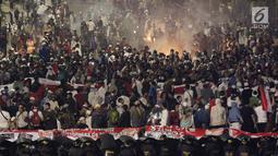 Massa aksi Gerakan Nasional Kedaulatan Rakyat mulai melakukan kericuhan usai berbuka puasa dan salat maghrib berjemaah di perempatan sekitar Gedung Bawaslu, Jakarta, Rabu (22/5/2019). (Liputan6.com/Helmi Fithriansyah)
