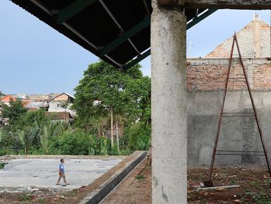 Anak-anak bermain di RPTRA Pelangi Cipedak yang pembangunannya terhenti di Jakarta, Senin (18/3). Terhentinya pembangunan RPTRA yang telah tiga kali mangkrak dikeluhkan warga karena molor dari target yang ditentukan. (Liputan6.com/Immanuel Antonius)