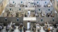 Petugas medis dan pasien terlihat di ruang perawatan rumah sakit sementara untuk pasien virus corona COVID-19 di Istana Es Krylatskoe di Moskow, Rusia, Rabu (18/11/2020). Otoritas Moskow mengubah arena seluncur es menjadi rumah sakit sementara untuk menangani pasien COVID-19. (AP/Pavel Golovkin)