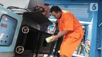 Tersangka memasukkan barang bukti narkoba jenis sabu ke dalam mesin pemusnah di Kantor BNN, Cawang, Jakarta, Selasa (4/2/2020). BNN memusnahkan sabu seberat 51,79 kg hasil penindakan di Medan, Sumatera Utara serta menangkap satu tersangka berinisial Zul. (Liputan6.com/Herman Zakharia)