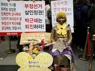 Wanita berdandan seperti patung untuk mewakili korban seksual militer Jepang pada Perang Dunia II di depan Kedutaan Besar Jepang, Seoul, Korea Selatan, (30/12). Mereka melakukan aksi Anti - Jepang selama beberapa pekan ini. ( REUTERS/Kim Hong - Ji)