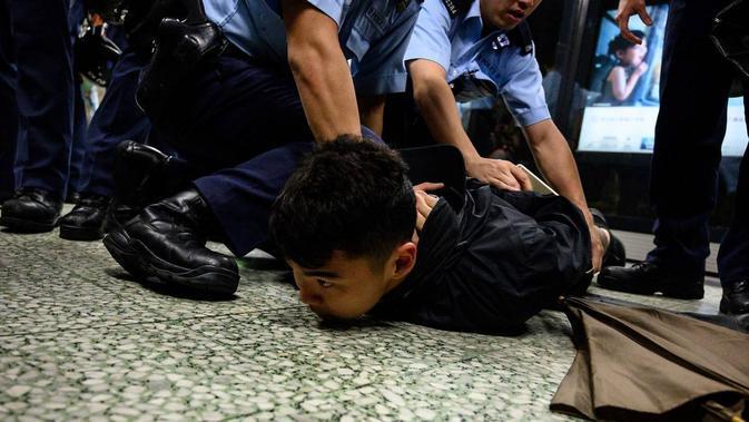 Polisi Hong Kong mengamankan seorang pengunjuk rasa di stasiun MTR Hong Kong di Lok Fu (Philip Fong / AFP PHOTO)