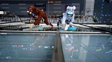 Dua petugas sedang membersihkan kaca jendela  sebuah hotel sambil mengenakan kostum babi hutan dan tikus di Tokyo, Kamis (19/12/2019). Hal ini mereka lakukan untuk merayakan bahun baru Imlek 2019 di Tahun Babi Tanah dan menyambut Tahun Tikus pada 2020. (AP Photo/Eugene Hoshiko)
