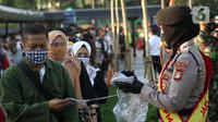 Personel polisi membagikan masker kepada calon penumpang kereta di area pedestrian Stasiun Terpadu Tanah Abang, Jakarta, Kamis (27/8/2020). Guna menekan penyebaran Covid-19, Polda Metro Jaya dan Kodam Jaya terus mengampanyekan pentingnya menaati protokol kesehatan. (Liputan6.com/Helmi Fithriansyah)