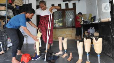 Ortotis prostetis atau pembuat kaki tangan palsu memasangkan kaki palsu buatannya kepada penyandang disabilitas di sebuah bengkel kawasan Ciputat Baru, Tangerang Selatan, Banten, Senin (14/10/2019). Kaki dan tangan palsu dijual dengan harga Rp 5 juta hingga Rp 50 juta. (merdeka.com/Arie Basuki)