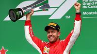 Pembalap Ferrari, Sebastian Vettel, meraih podium juara pada balapan Formula 1 GP Kanada, di Sirkuit Montreal, Minggu (10/6/2018). (AFP/Dan Istitene)