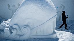 Seorang seniman mengukir patung es raksasa berbentuk ikan di Snow Land, PyeongChang, Korea Selatan, Senin (5/2). (Brendan Smialowski/AFP)