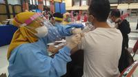 Tenaga medis menyuntikkan vaksin Covid-19 ke mahasiswa luar daerah yang sedang belajar di Malang. Program ini demi membantu percepatan vaksinasi di Malang (Liputan6.com/Zainul Arifin)