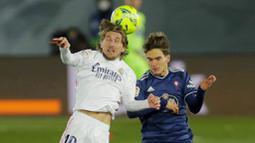 Gelandang Real Madrid, Luka Modric, duel udara dengan pemain Celta Vigo, Denis Suarez, pada laga Liga Spanyol di Stadion Alfredo Di Stefano, Sabtu (2/1/2021). Real Madrid menang dengan skor 2-0. (AP/Manu Fernandez)