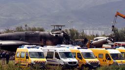 Tim medis bersama petugas kebakaran mencari korban di reruntuhan pesawat tentara Aljazair yang jatuh di dekat pangkalan udara Boufarik, Aljazair (11/4). Sebagian besar korban adalah personel militer dan keluarga mereka. (AP Photo/Anis Belghoul)