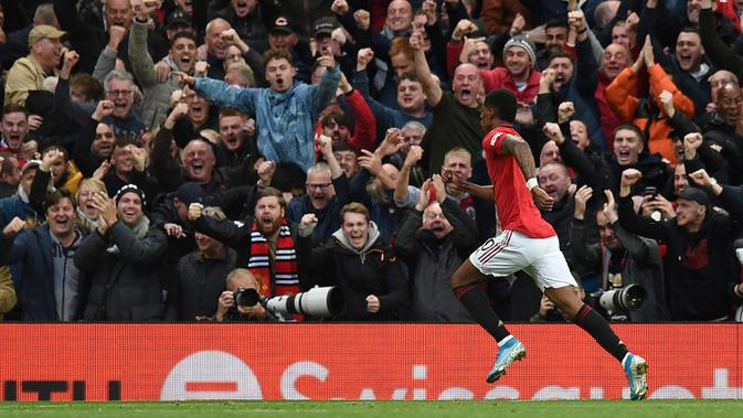 Striker Manchester United, Marcus Rashford, merayakan gol yang dicetaknya ke gawang Liverpool pada laga Premier League di Stadion Old Trafford, Manchester, Minggu (20/10). Kedua klub bermain imbang 1-1. (AFP/Oli Scarff)