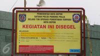 Sebuah plang penyegelan dipasang di tempat ibadah jemaah Ahmadiyah di Sawangan, Depok, Jumat (24/2). Beredar kabar melalui pesan berantai bahwa tempat ibadah tersebut akan ditutup paksa. (Liputan6.com/Immanuel Antonius)