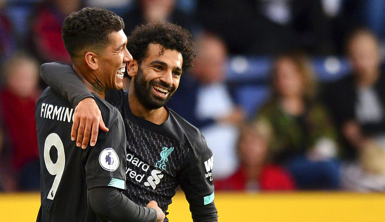 Striker Liverpool, Roberto Firmino, melakukan selebrasi bersama Mohamed Salah usai membobol gawang Burnley pada laga Premier League 2019 di Stadion Turf Moor, Sabtu (31/8). Liverpool menang 3-0 atas Burnley. (AP/Anthony Devlin)
