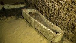 Mumi terbungkus kain linen ditemukan di ruang pemakaman di Provinsi Minya, Mesir, Sabtu (2/2). Usia mumi tersebut diperkirakan lebih dari 2.000 tahun. (AP Photo/Roger Anis)