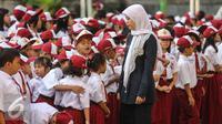 Guru mengatur para murid sebelum upacara di SD Pasar Baru 05, Jakarta, Senin (27/7/2015). Usai libur panjang Idul Fitri para siswa kembali beraktivitas mengikuti pelajaran di sekolah untuk tahun ajaran 2015-2016. (Liputan6.com/Faizal Fanani)