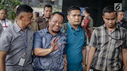 Anggota DPRD Provinsi Jambi Supriyono menyapa awak media saat dibawa ke Gedung KPK, Jakarta, Rabu (29/11). Dalam operasi senyap yang dilakukan KPK kemarin, ada sekitar 11 orang yang diciduk di Jambi dan Jakarta. (Liputan6.com/Faizal Fanani)