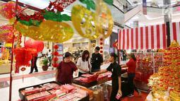 Pengunjung membeli pernak-pernik Imlek di atrium Lippo Mall Puri, Jakarta, Jumat (01/2). Aneka bazar dan kuliner memenuhi kebutuhan keluarga untuk merayakan Tahun Baru Imlek. (Liputan6.com/Fery Pradolo)