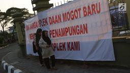 Pencari suaka melintasi spanduk penolakan di depan bekas Markas Kodim di Kalideres, Jakarta, Selasa (16/7/2019). Sejak Kamis (11/7) para pencari suaka dipindahkan dari di pinggir jalan dan trotoar di kawasan Kebon Sirih ke bekas Markas Kodim di Kalideres . (Liputan6.com/Helmi Fithriansyah)