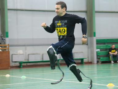 Seorang prajurit bernama Vadym Svirydenko berlari menggunakan kaki palsu saat mengikuti tes untuk turnamen Invictus Games Ukraine di Kiev, Ukraina (28/1). (AP Photo/Efrem Lukatsky)