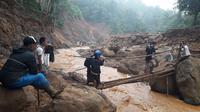 Relawan mendistribusikan logistik dengan akses terbatas untuk korban longsor di Kecamatan Sukajaya, Bogor. (Achmad Sudarno/Liputan6.com)