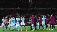 Para pemain Manchester City merayakan kemenangan usai pertandingan melawan Manchester United pada Liga Inggris di Old Trafford Stadium, Inggris, (10/12). City menang atas MU 2-1. (AFP Photo/Oli Scarff)