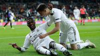 Striker Real Madrid, Vinicius Junior (kiri) berselebrasi setelah mencetak gol ke gawang Leganes pada laga leg pertama babak 16 besar Copa del Rey di Santiago Bernabeu, Rabu (9/1). Real Madrid sukses mengandaskan Leganes dengan skor 3-0 (AP/Manu Fernandez)
